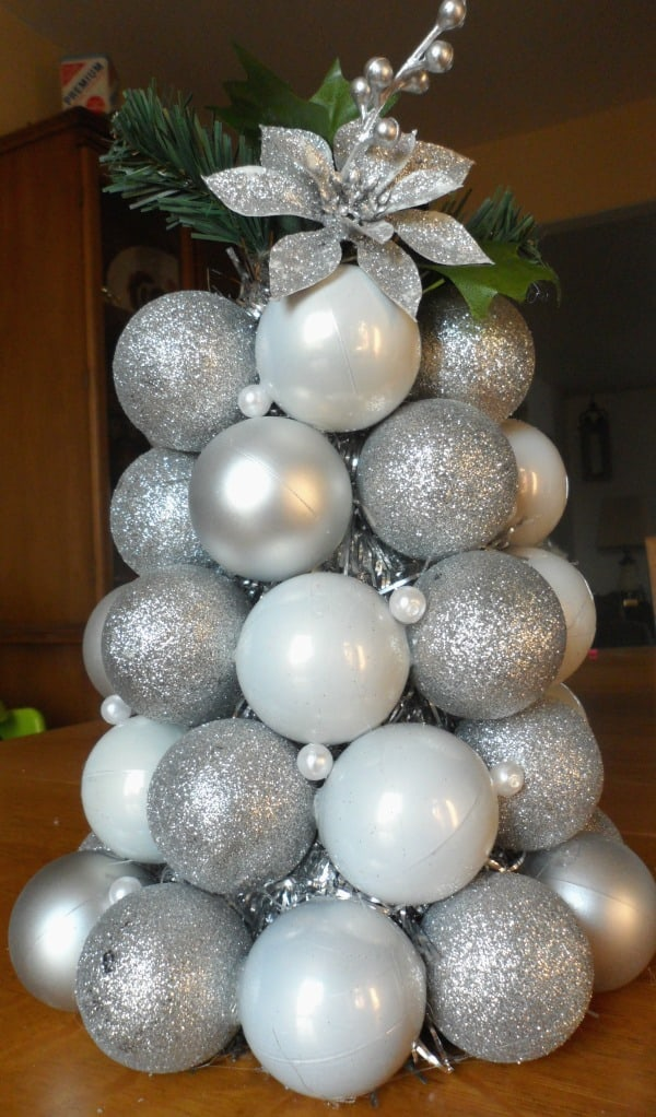 If you are looking for an easy craft to make to decorate your home for the holidays, then consider making this festive ornament tree made from Christmas ball ornaments.