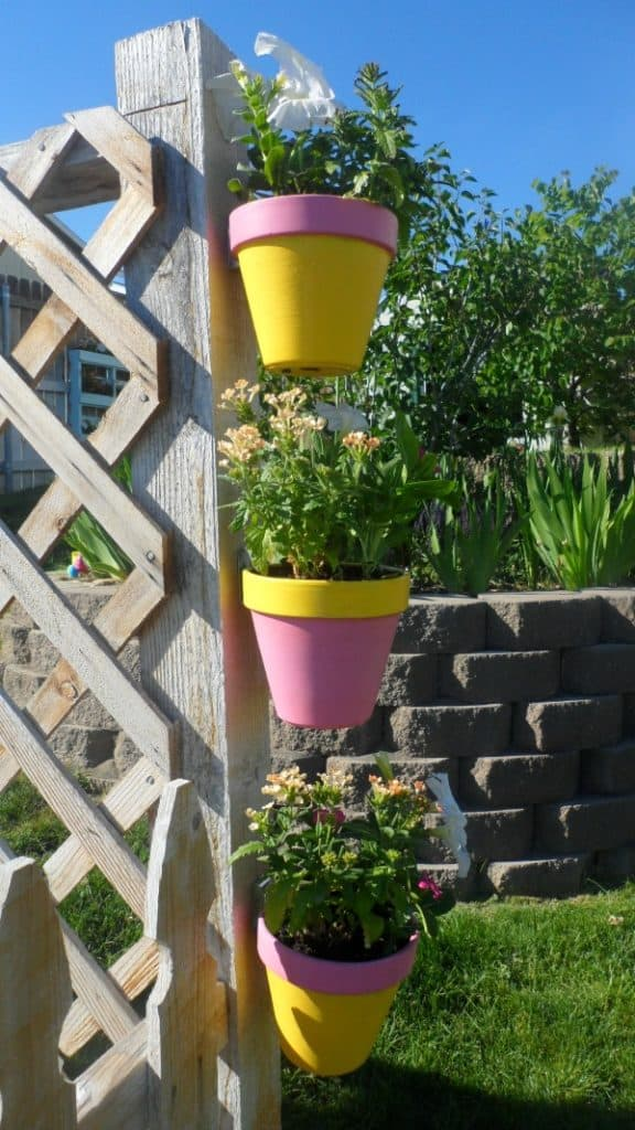 Easy DIY idea for hanging a painted flower pot on a fence.