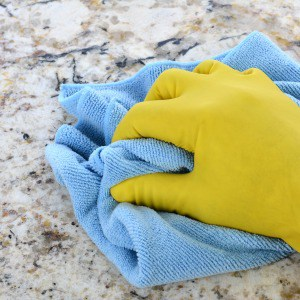 Person wearing rubber gloves cleaning a granite countertop