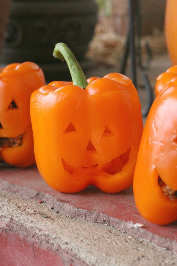 Easy Halloween dinner idea! Make these Halloween stuffed peppers mexican style, with spaghetti, or vegetarian.