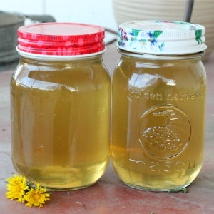 Two pint jars of homemade dandelion syrup sitting on the front porch.